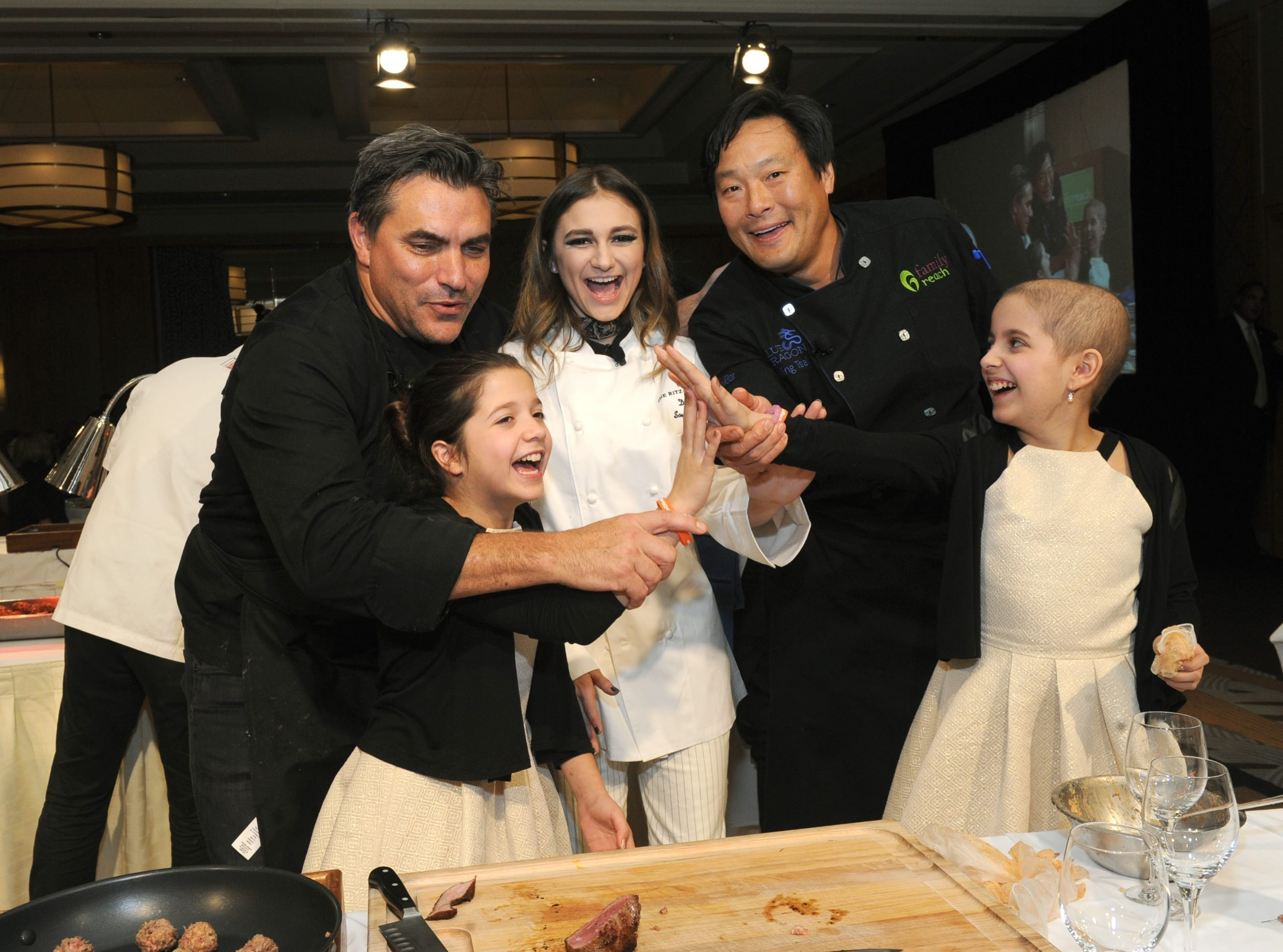 Todd English, Daya (singer/songwriter) and Ming Tsai prepare the fourth course of the evening with twins Olivia and Sabrina. Olivia is currently battling a rare form of leukemia and Sabrina is her bone marrow donor.