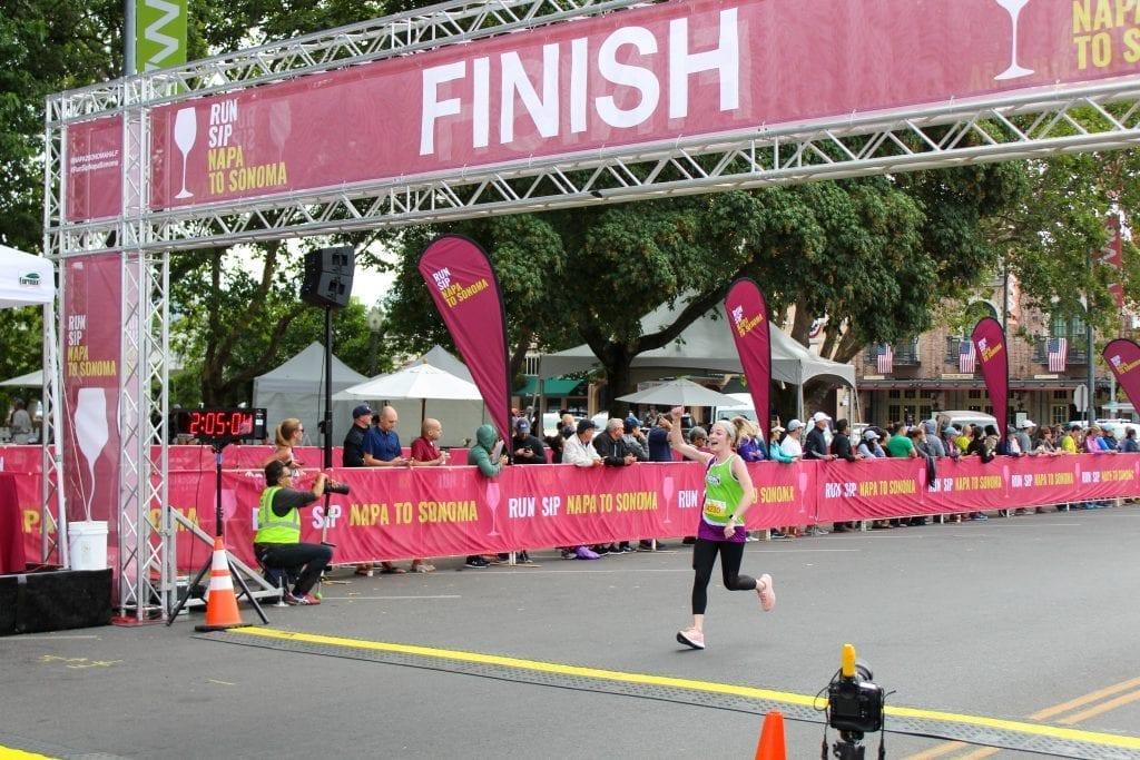 Kasey running through the finish line