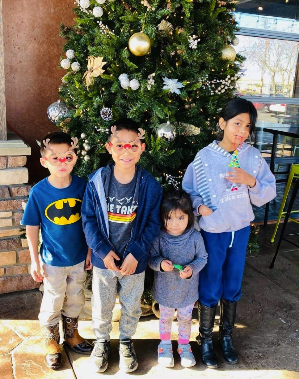 Cancer hero Ruben with his siblings in front of a Christmas tree