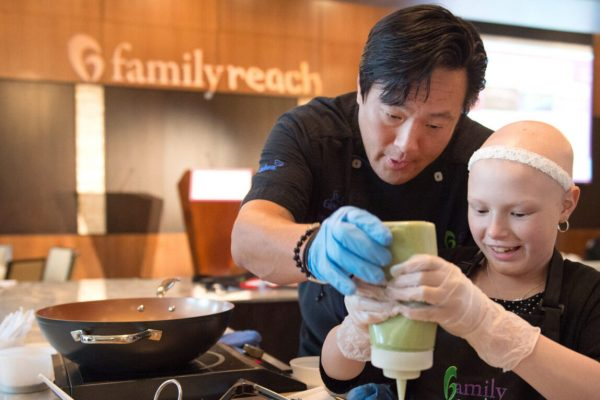 Chef Ming Tsai, assists Ashlynn Hull, 11,  in putting the final touch on a duck flatbread with avocado puree and pineapple salsa,  during the Family Reach fundraising event,