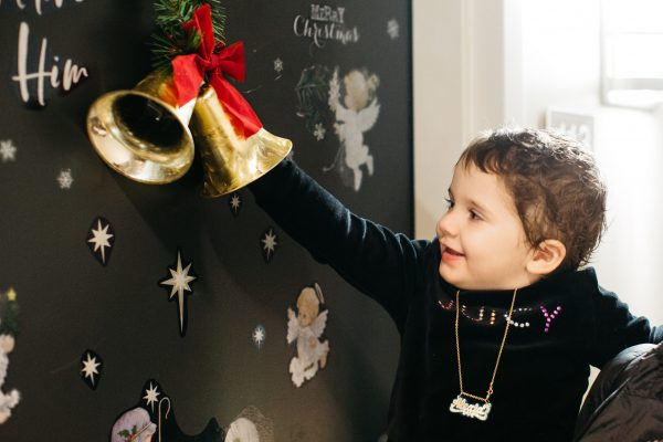 Pediatric cancer patient ringing holiday bell