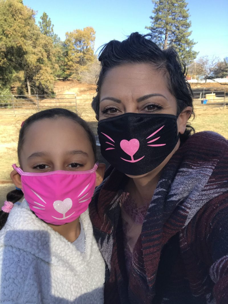 Cancer survivor Renee wearing cat face masks with her daughter