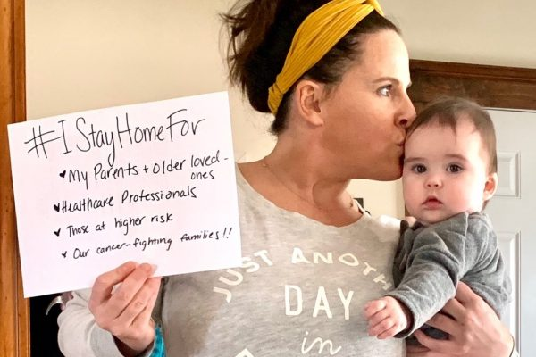 Family Reach staff member holding her baby and #IStayHomeFor paper sign