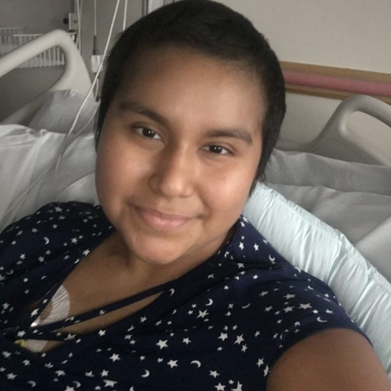 Cancer hero Vanessa smiling in hospital bed
